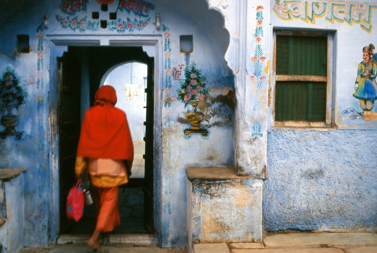 A woman enters a house in India.