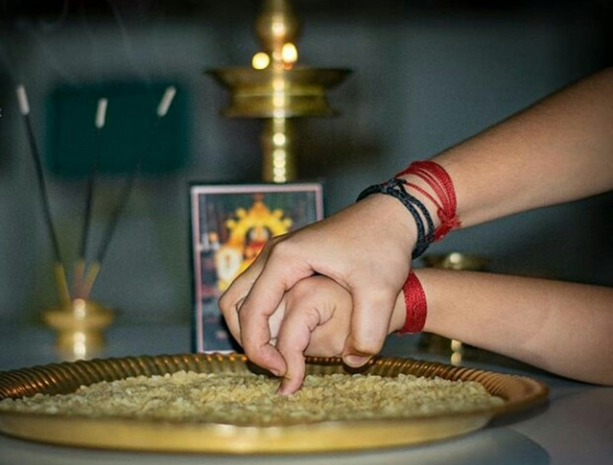 A scholar guides a child's hand as they write their mantra on a platter of rice.
