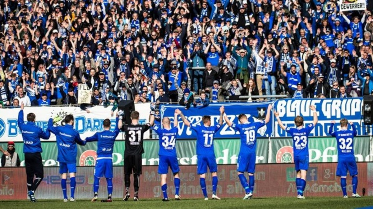 SV Darmstadt 98 players celebrate with fans inside Stadion Böllenfalltor in Darmstadt, Germany in 2016. The 2015-16 season marked the club's first foray in the Bundesliga in 33 years.