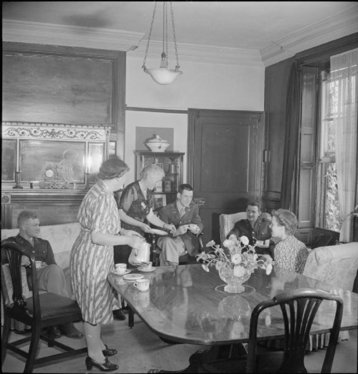 Photograph of American soldiers having afternoon tea in Winchester, England. (ca. 1944). Photographer unknown, of the Ministry of Information Photo Division. Work is in the public domain.