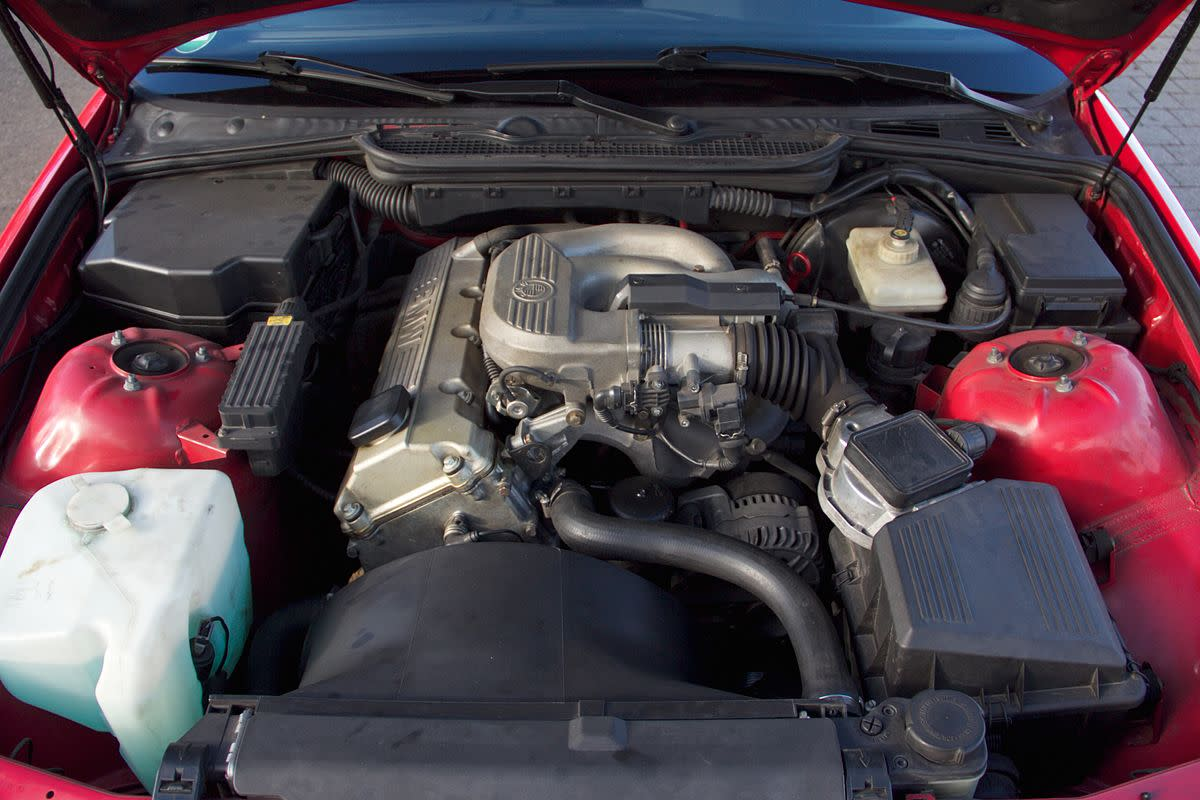 Radiator shroud, upper radiator hose, and coolant reservoir (left) are typical cooling system components.