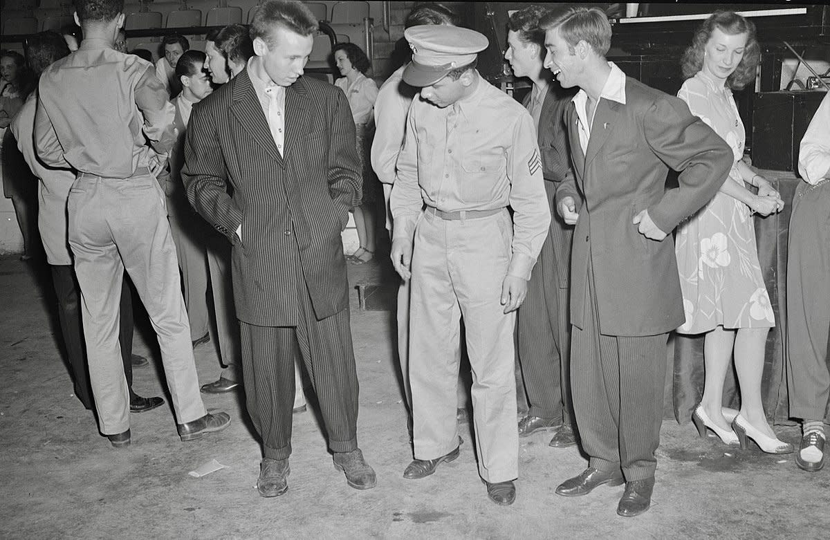 A soldier seems unimpressed by the zoot suits worn by a couple of young men in 1942.