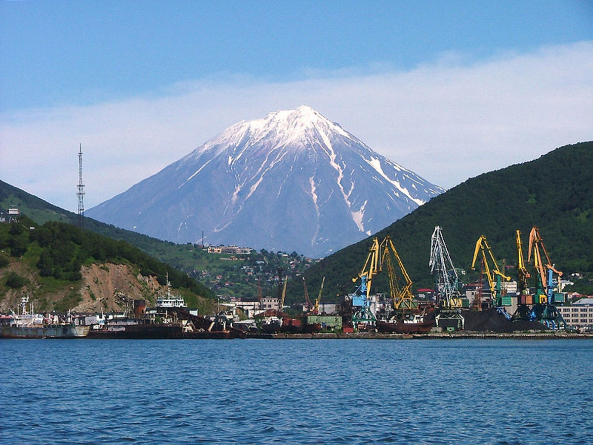 The Russian harbor of Petropavlovsk-Kamchatsky as seen from Avacha Bay. Snow-capped Mount Koryasky rises spectacularly in the background. This active volcano last erupted in 2009