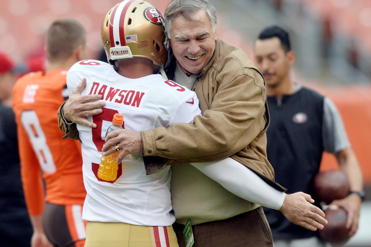 Former Cleveland Browns lineman and current radio announcer, Doug Dieken (right), embraces former Cleveland and San Francisco 49ers kicker, Phil Dawson, prior to a 2015 game at FirstEnergy Stadium.