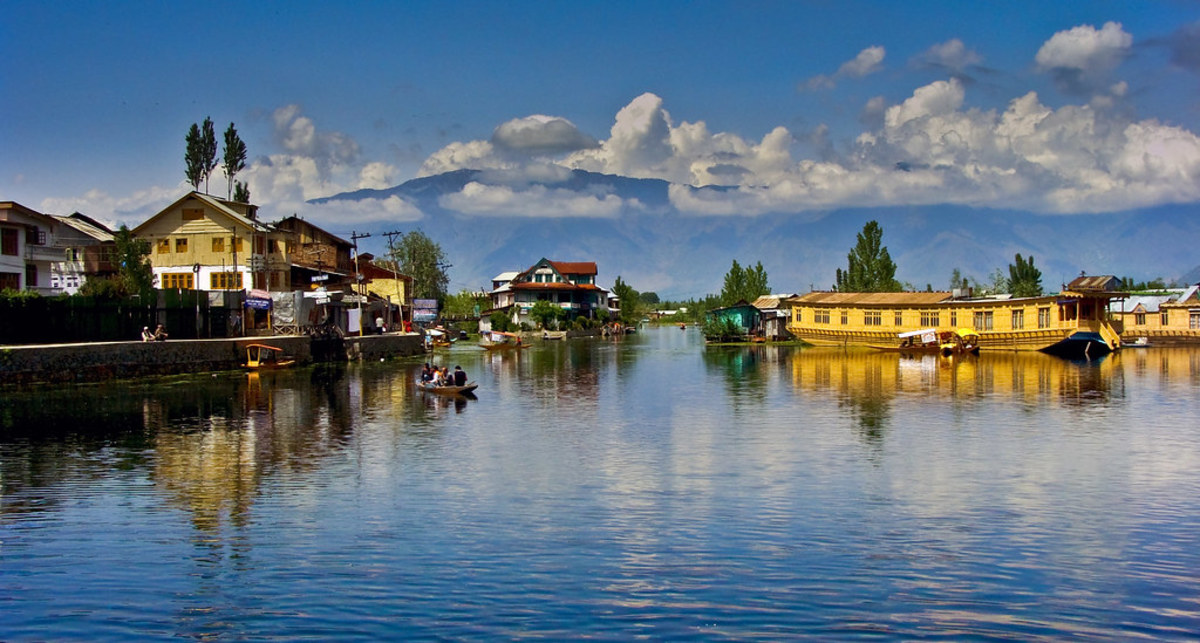The beautiful Dal Lake reflecting the carved wooden balconies of the houseboats and the misty peaks of the Pir Panjal mountains.