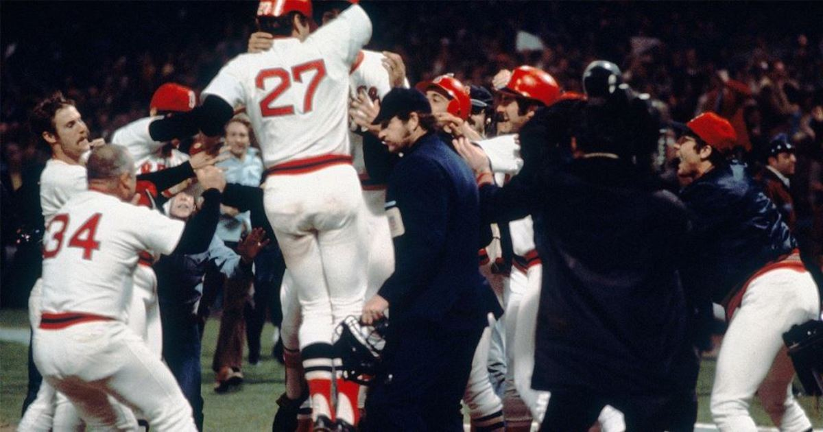 Carlton Fisk jumps on home plate and into the arms of his teammates.
