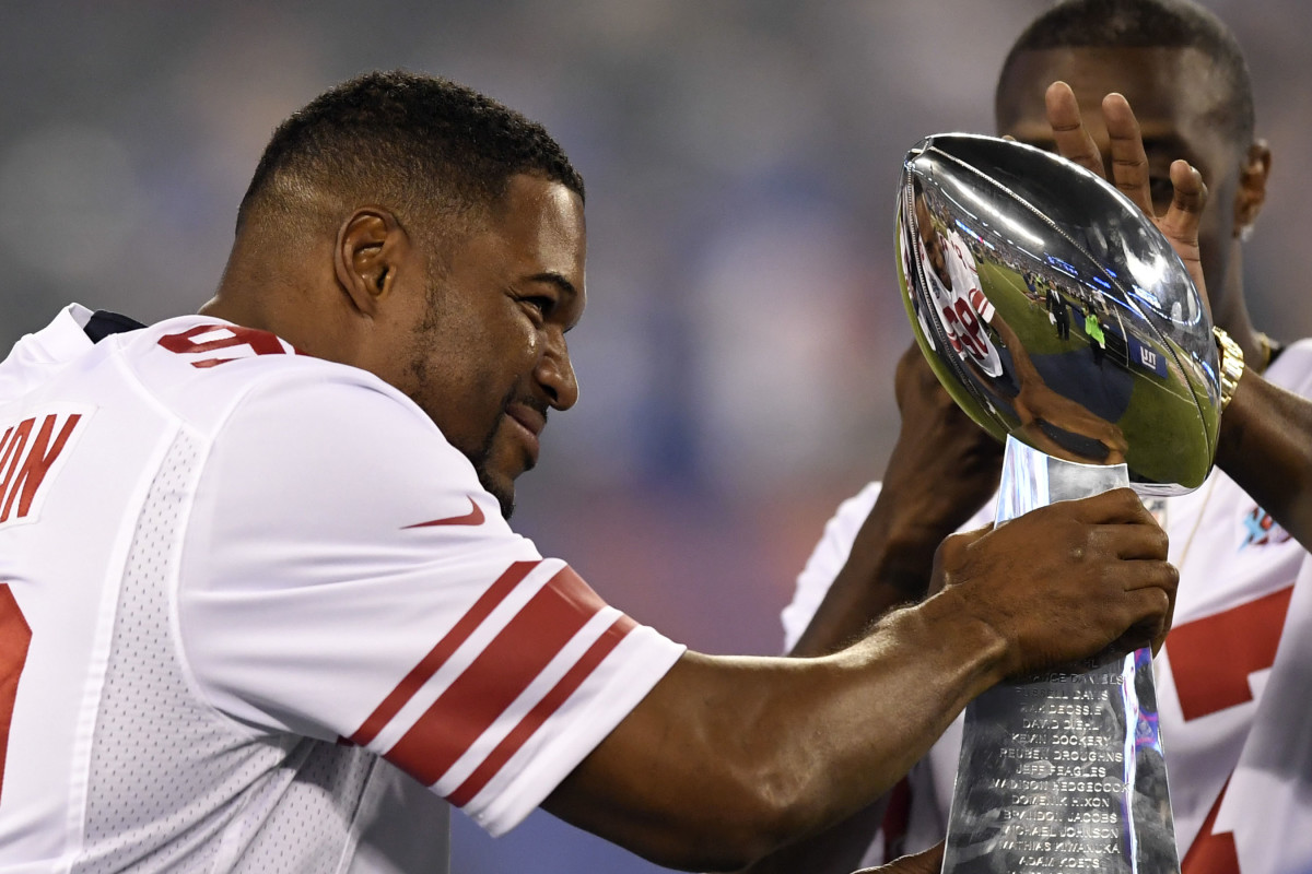 New York Giants former player Michael Strahan walks onto the field with the Vince Lombardi Trophy from Super Bowl XLII during the halftime ceremony in the game against the Detroit Lions at MetLife Stadium, Sept. 18, 2017