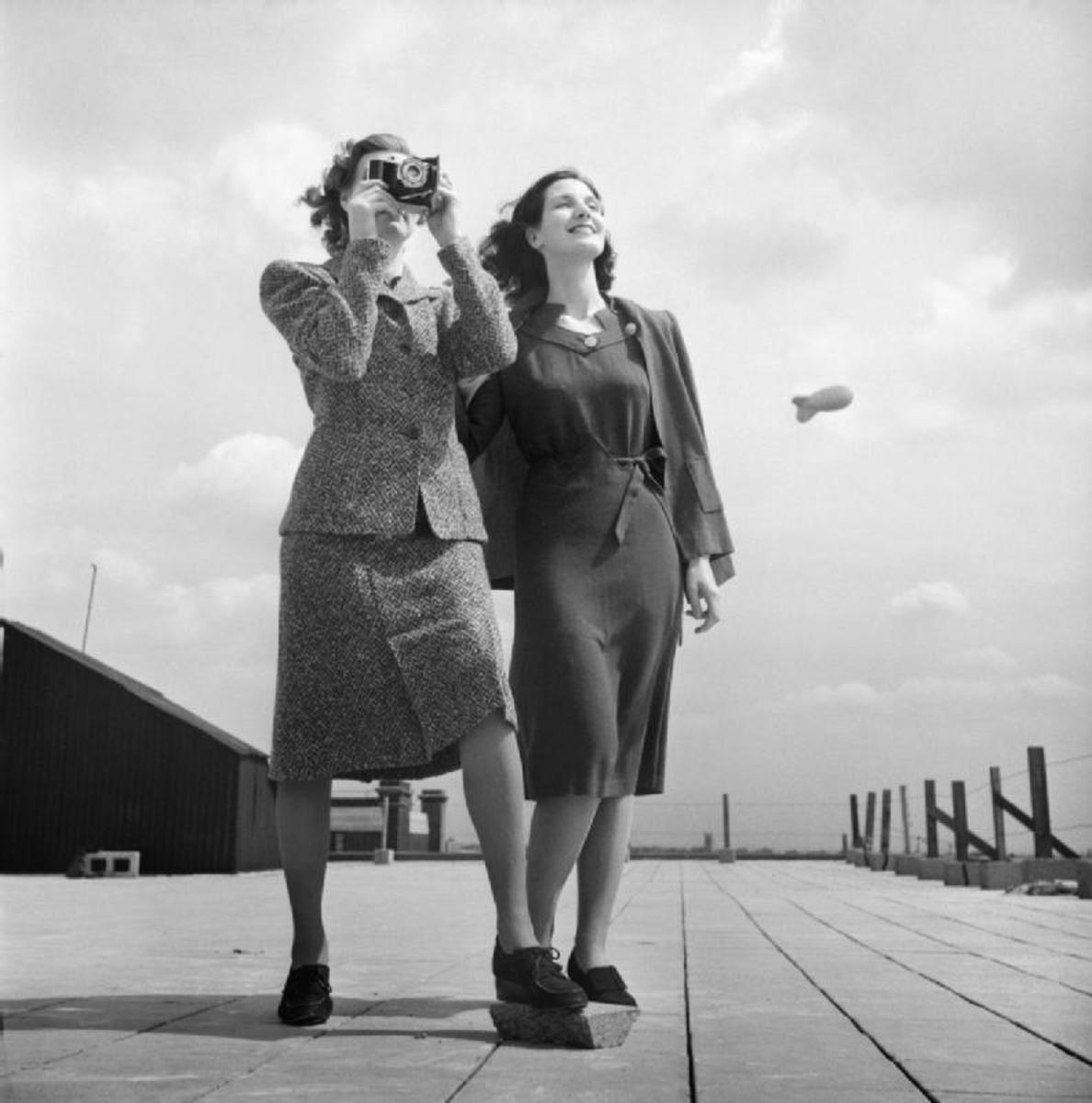 1943: The simple dresses of wartime featured short hemlines. There is a barrage balloon in the background.