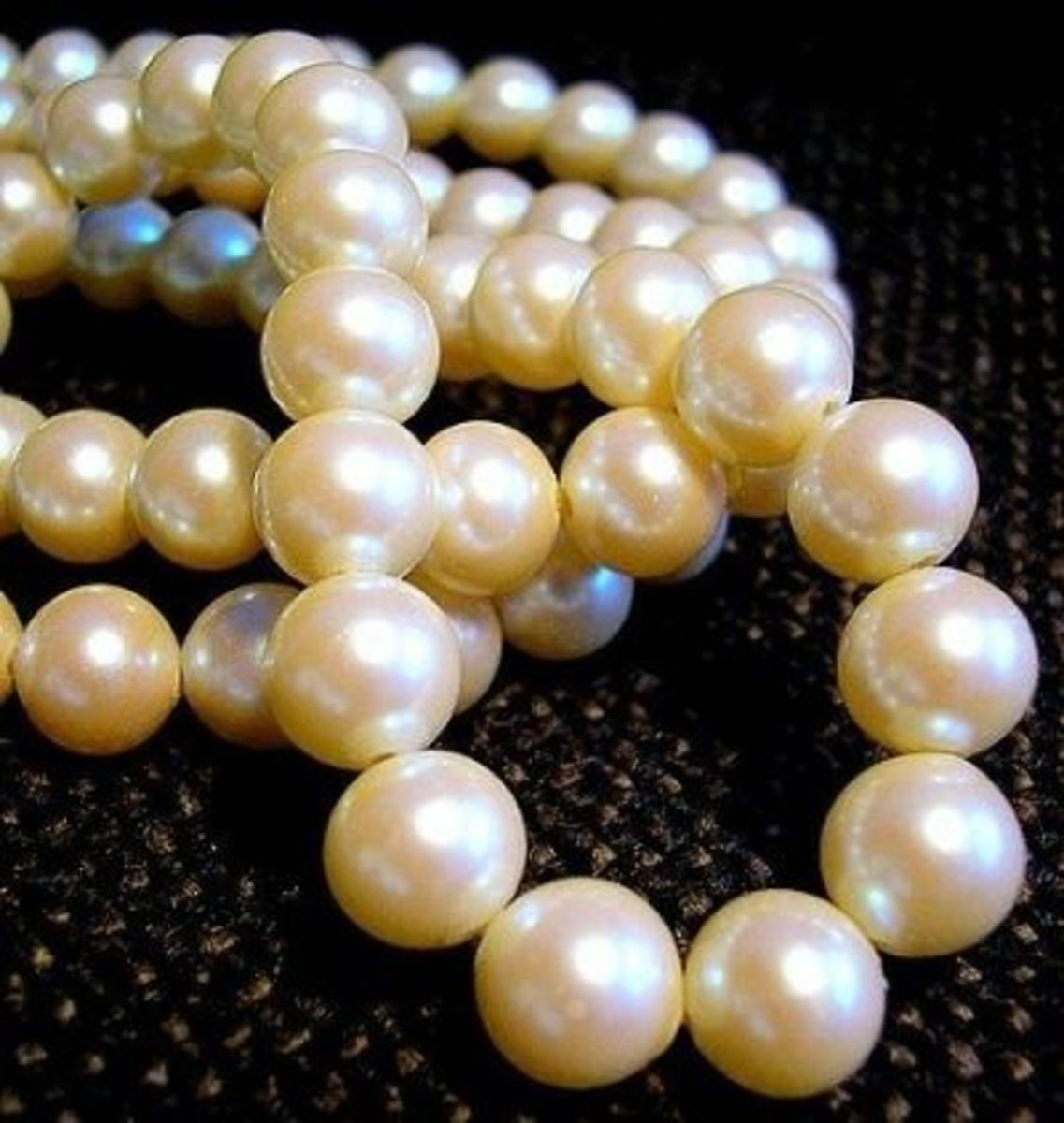 ... and they are more valuable than the pearls in the previous photo because they are well-matched in size, shape, and color. (These are genuine but unstrung and that's probably why they aren't yet knotted.)
