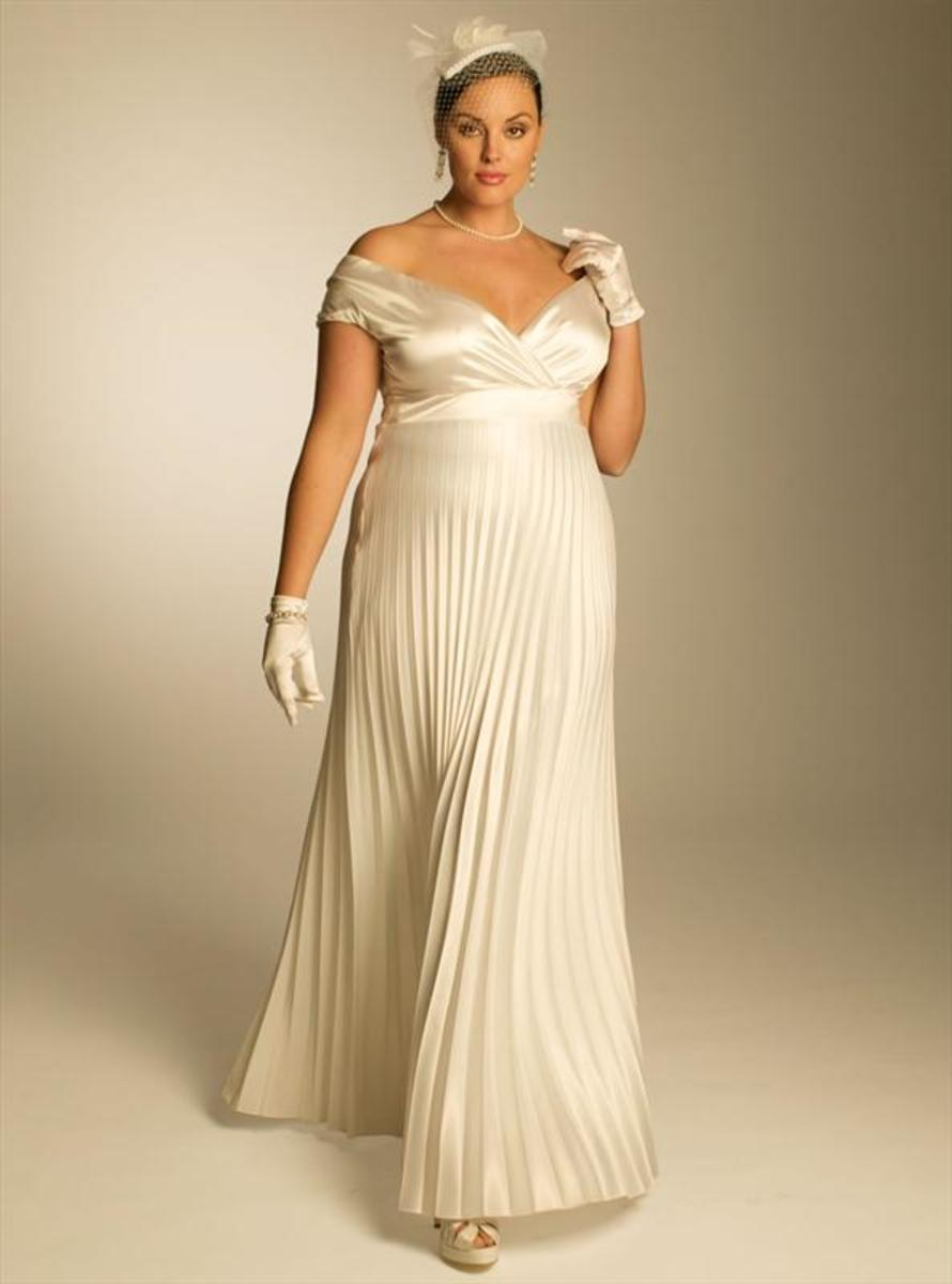 Evelin pleated gown. A jaw-dropping, statuesque wedding dress with columns of pleats, exuding purity and elegance in luxurious stretch satin and peeking open neckline.
