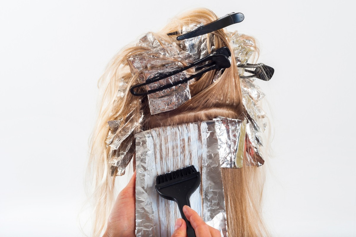 Brushing the dye into the hair with a tinting comb. The foil acts almost like a canvas.