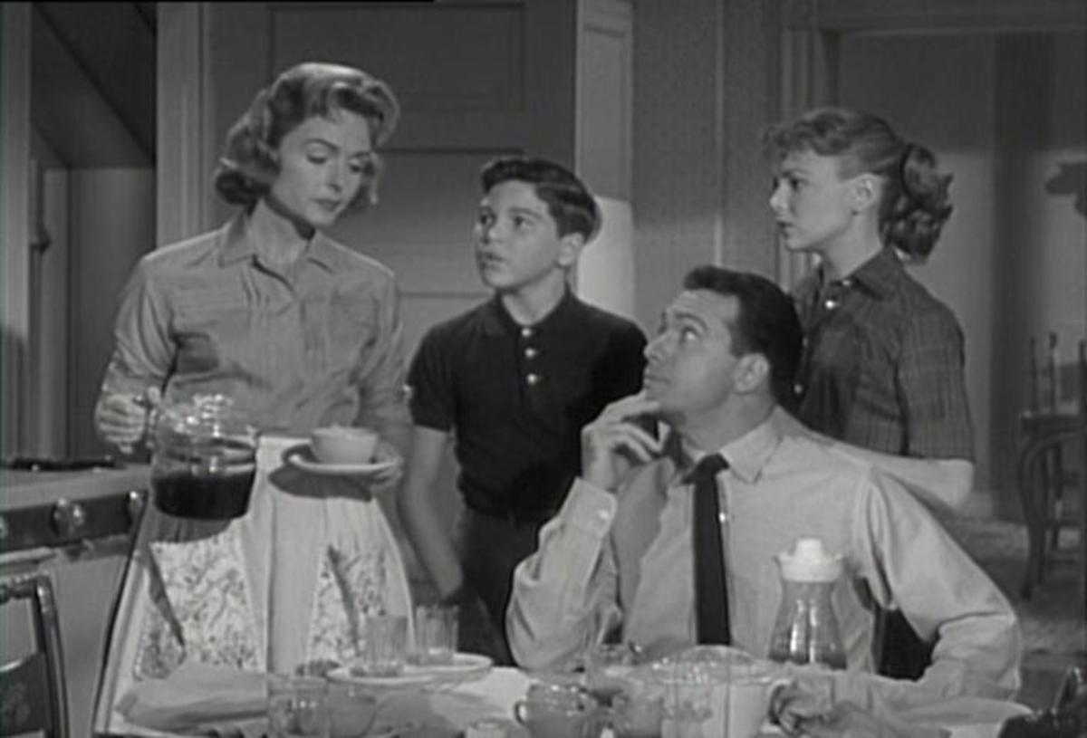 Donna Reed as the quintessential American housewife wearing an apron
