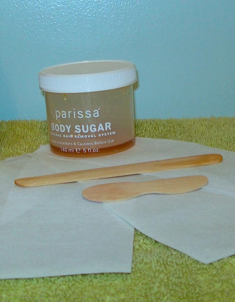 Body sugaring supplies: body sugar, applicator sticks and cloth strips