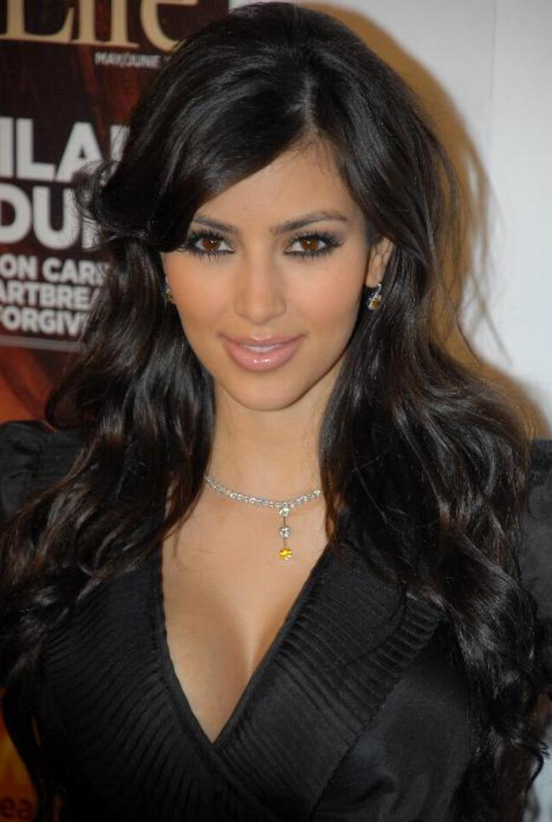 Kim Kardashian with wavy black hair and side bangs.
