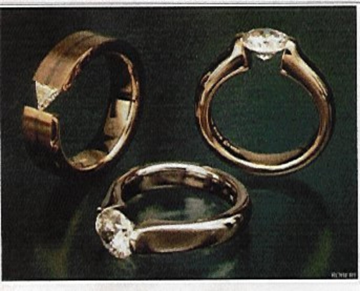 These classic solitaires from Stephen Kretchmer Designs are tension set. Note the absence of a base under the gemstone.