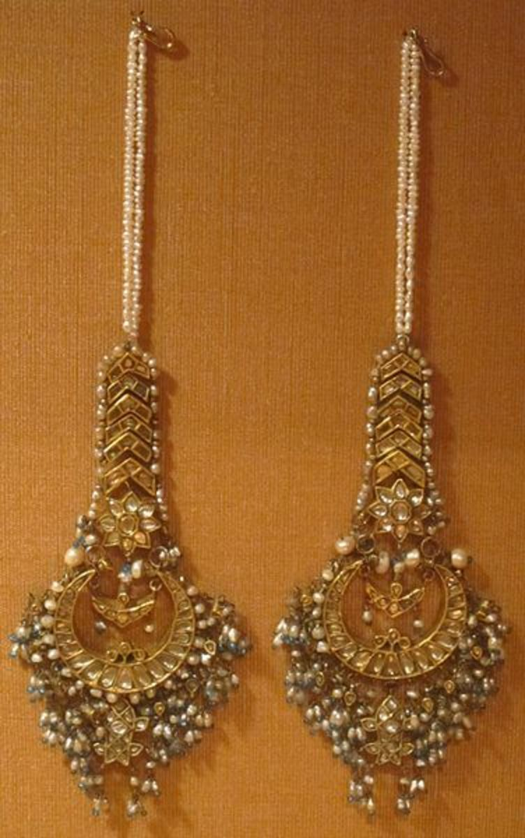 Mughal gold earrings strewn with gemstones, premium beads, and long strings of tiny pearls