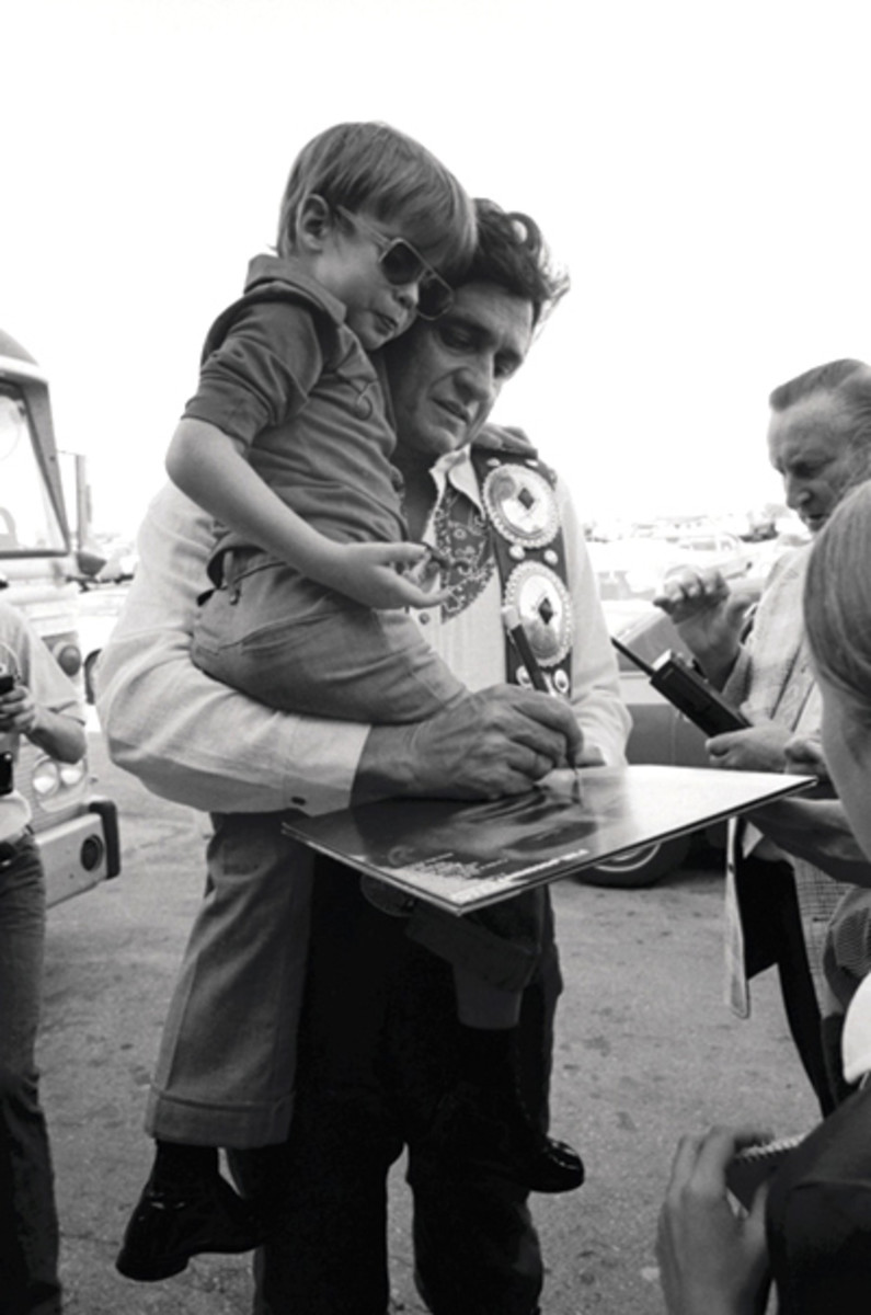 Johnny Cash holding a child with a concho belt wrapped over his shoulder