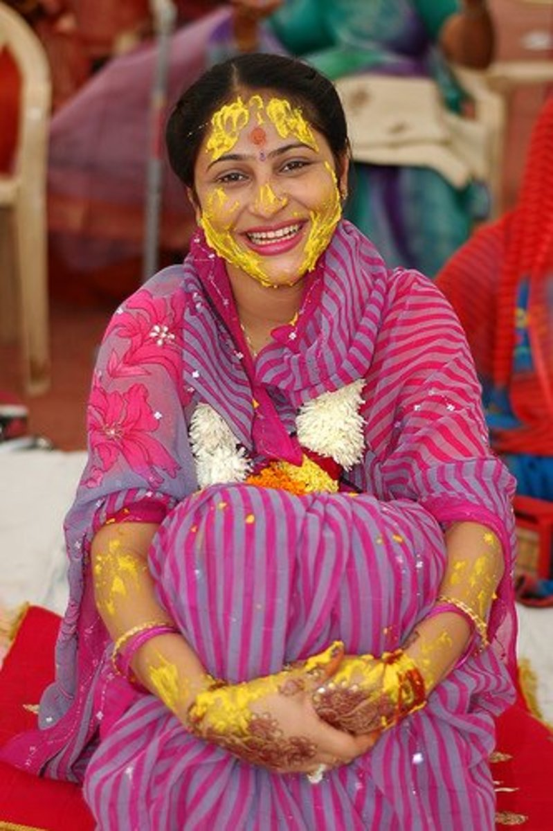 Indian bride-to-be with turmeric on her face and arms.