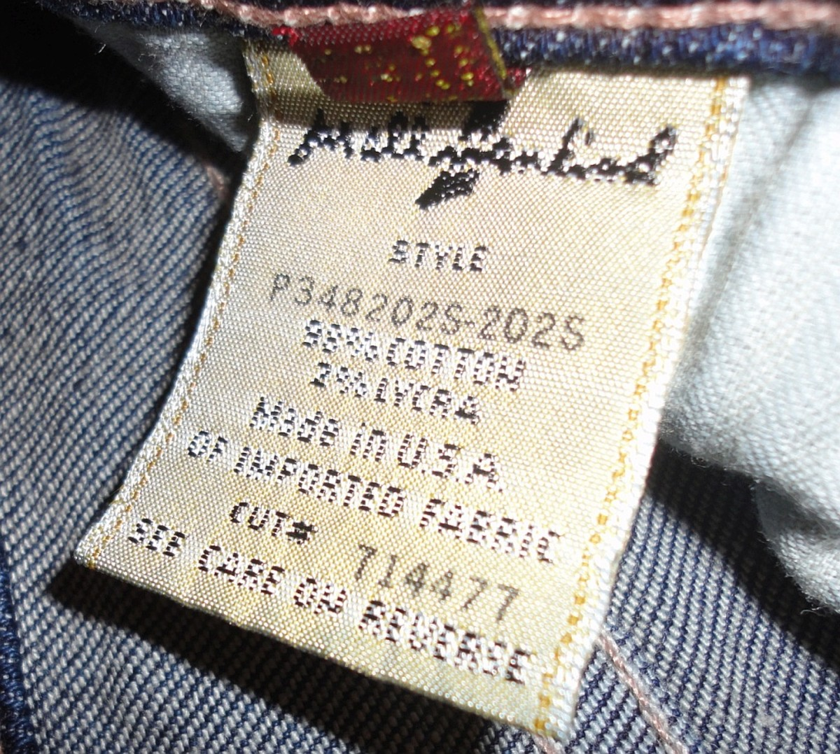 Looking at a genuine tag, one will see the style code [P348 ...] & cut # [714477] have been screen printed directly onto the tag. A fake pair of jeans would be stitched on, not printed.