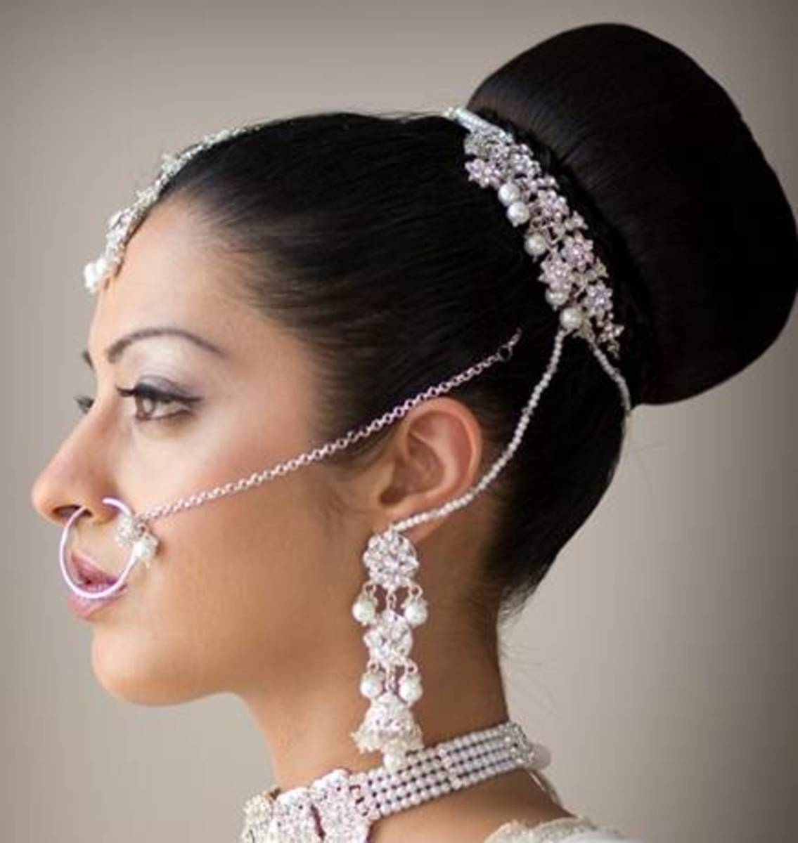 Flat-front hairdo with a big high hair bun for hanging the wedding dupatta.