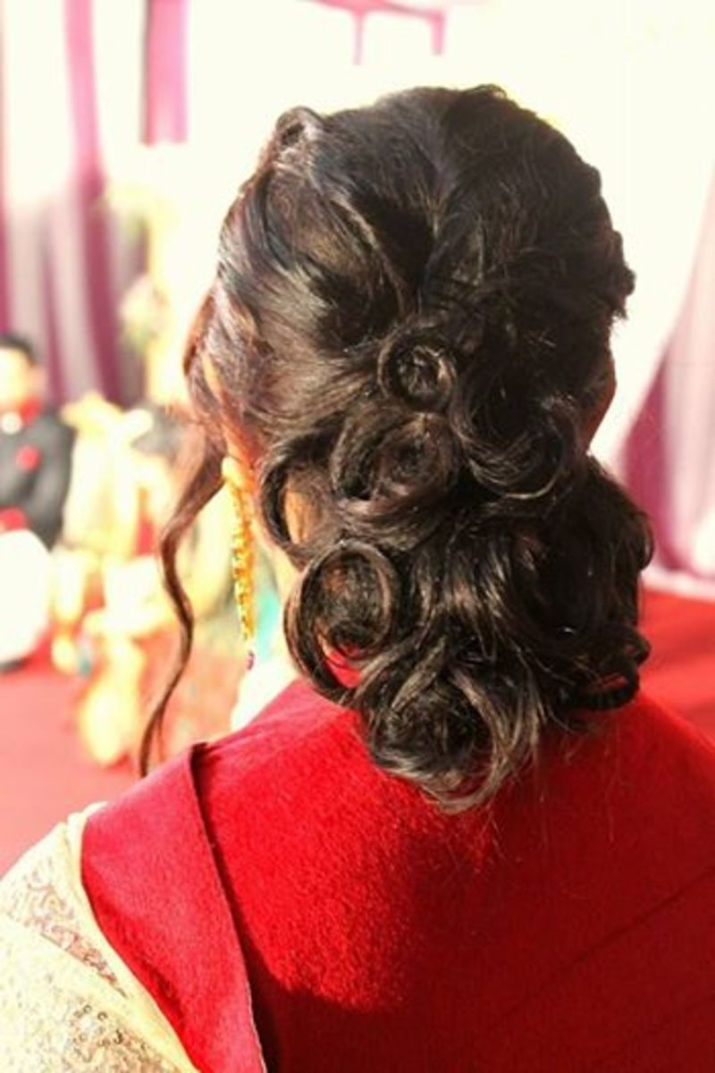 Low hair bun with clipped curls.