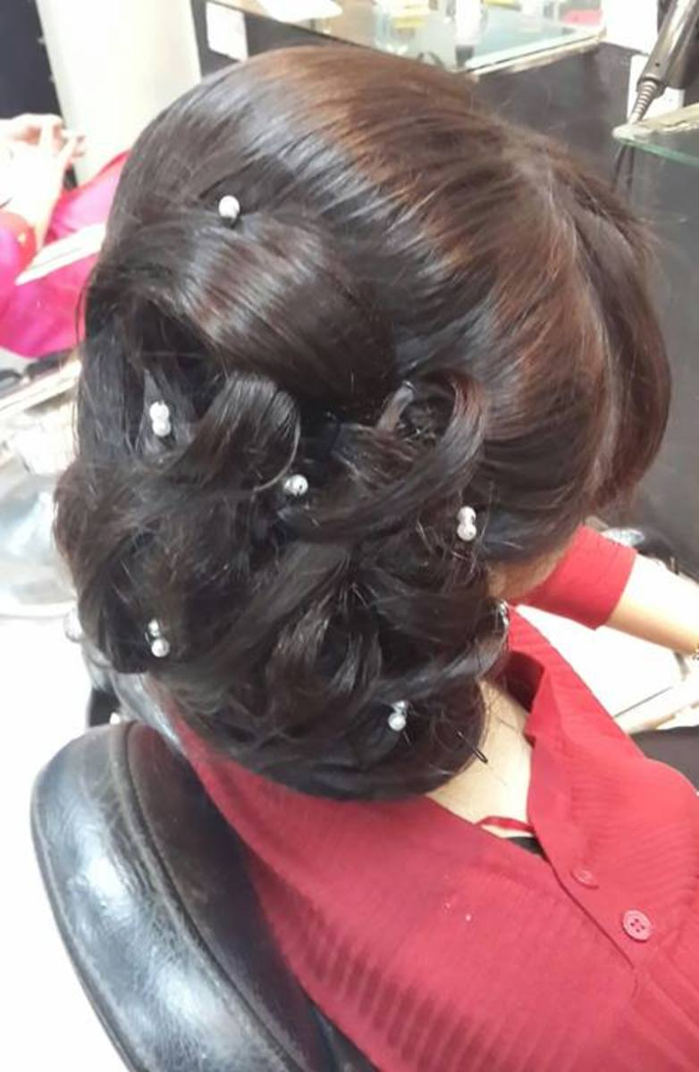 Back view of a hair bun with clipped curls and pearls.