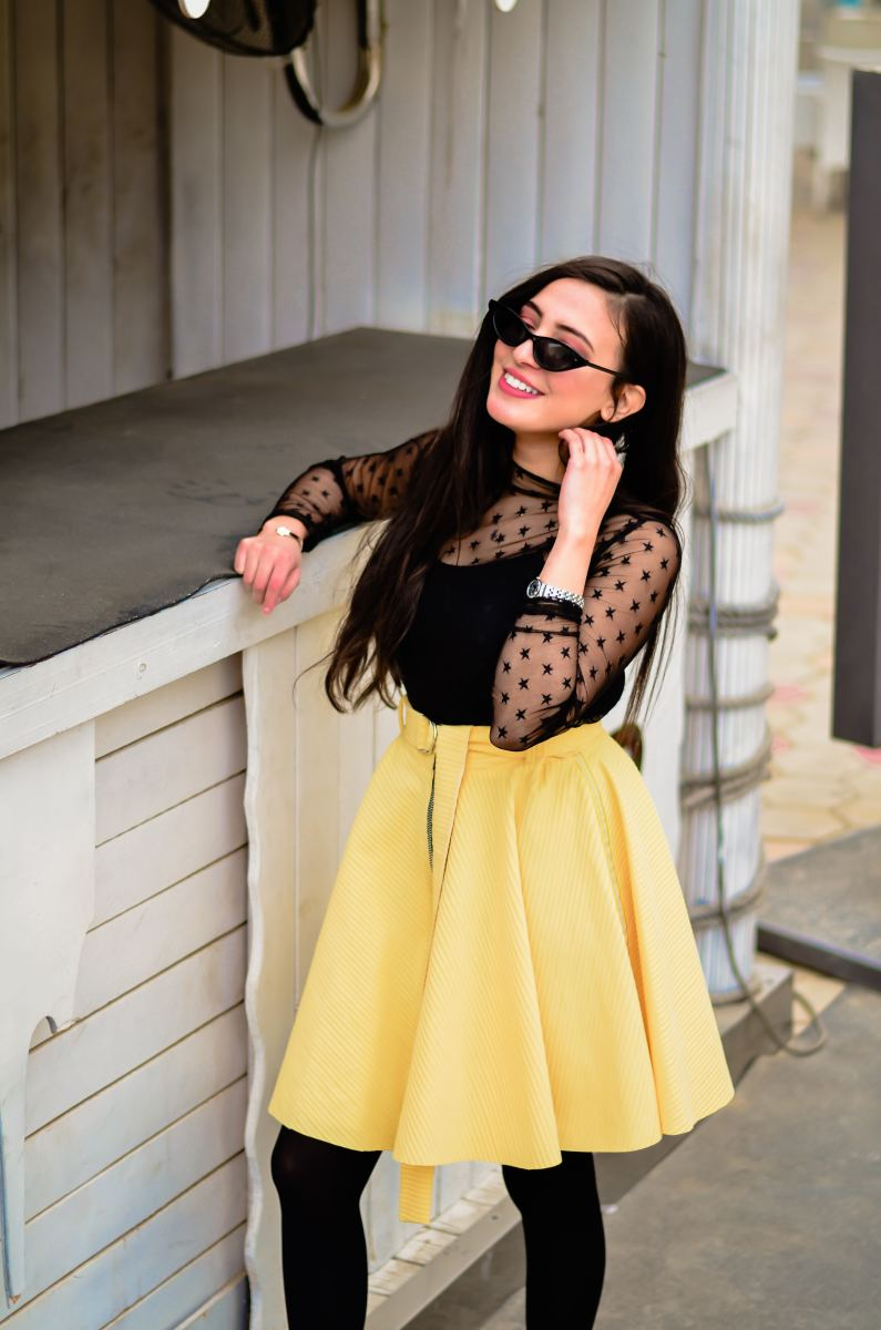 A skater skirt can be dressed up for a more casual wedding with a feminine chiffon top.