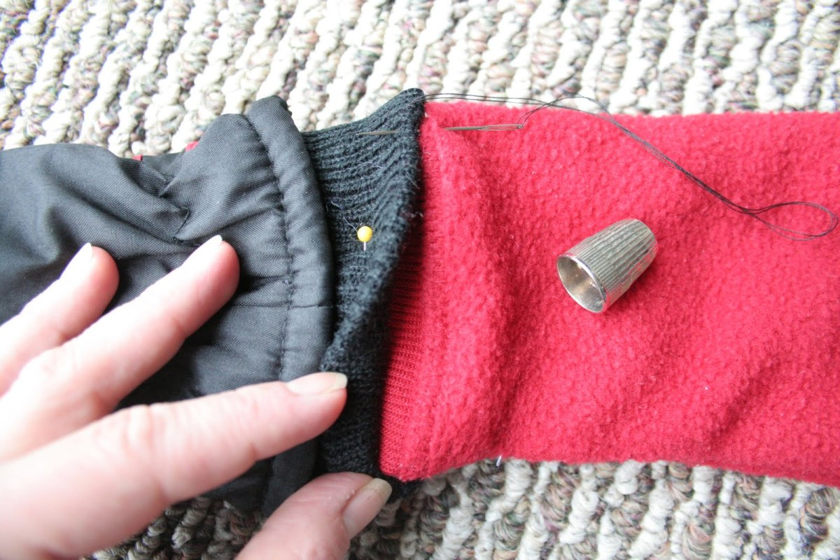 Sewing gloves to jacket sleeves.
