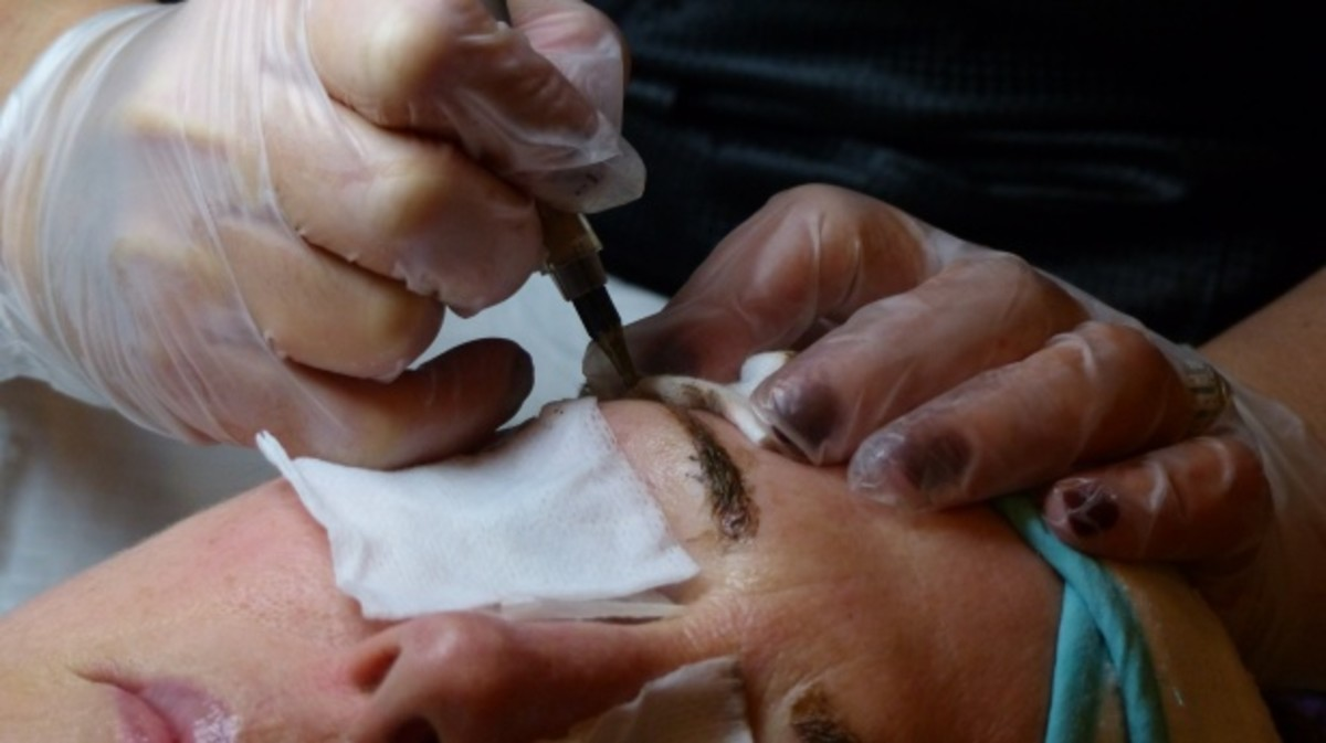 A beautician tattooist enhancing facial features with permanent makeup tattoos