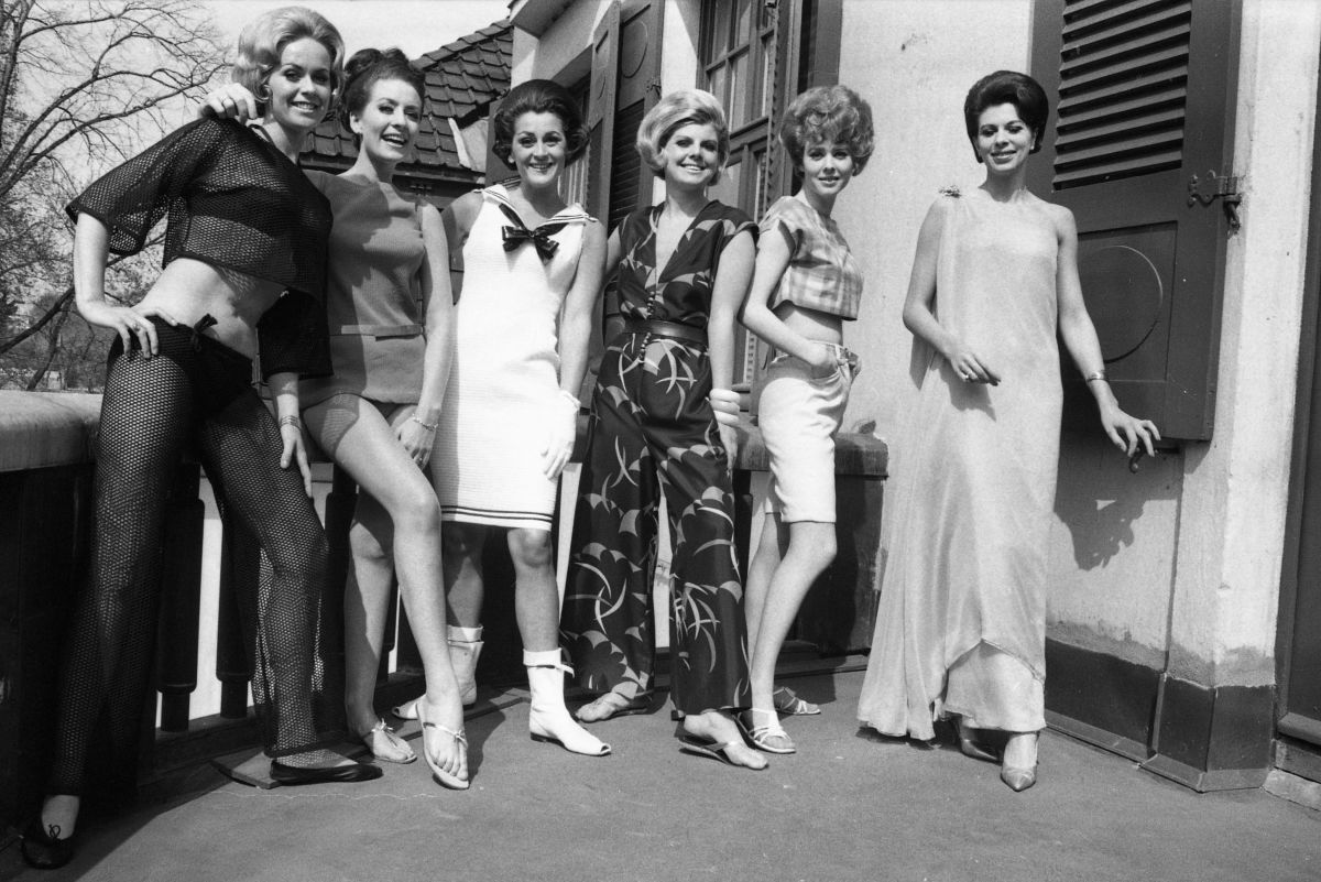 A wide variety of mid 60s styles including bouffant hair, short skirts, go-go boots, middriff top, and Bermuda shorts.