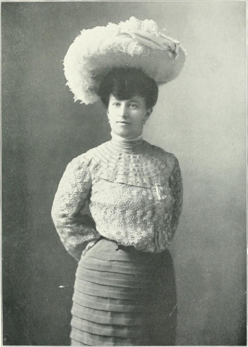 1900–1910: The huge hat on puffed hair, the loose fronted, yoked blouse decorated by tons of lace date this photo to the early 1900s.