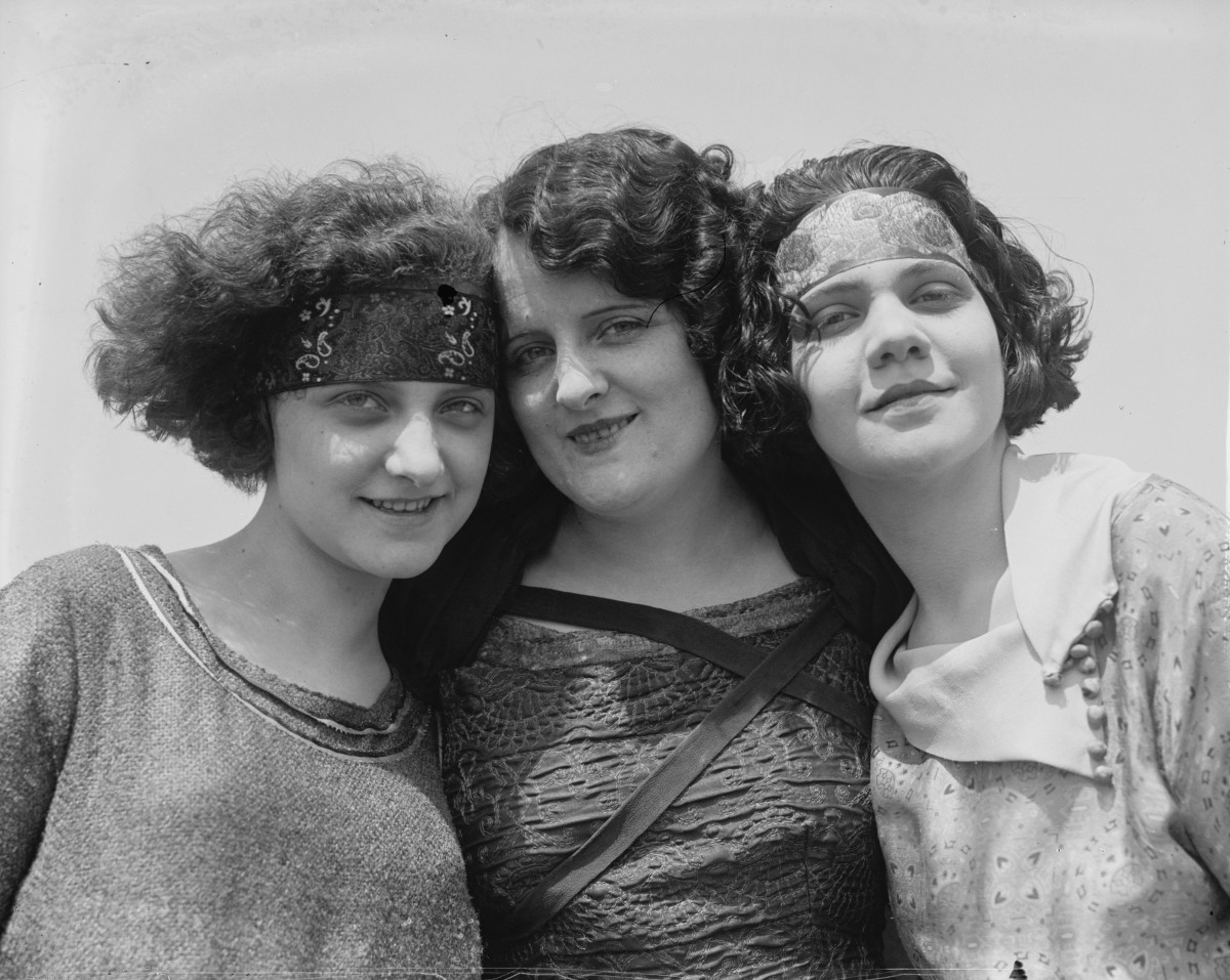 The crimped, bobbed hair; horizontal headbands; and jaunty air date this photo to the 1920s.