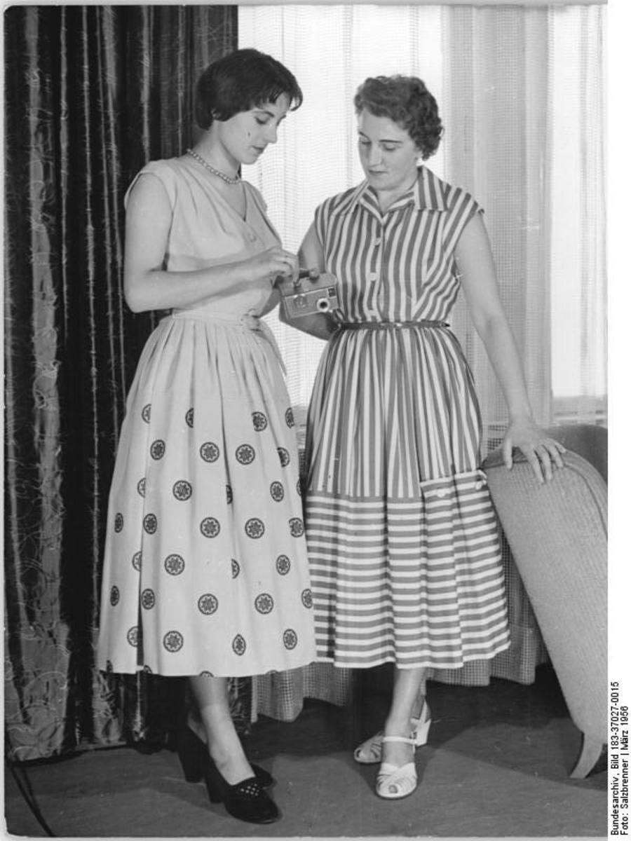 Short hair; longer and wider skirts date this pic to the 1950s.