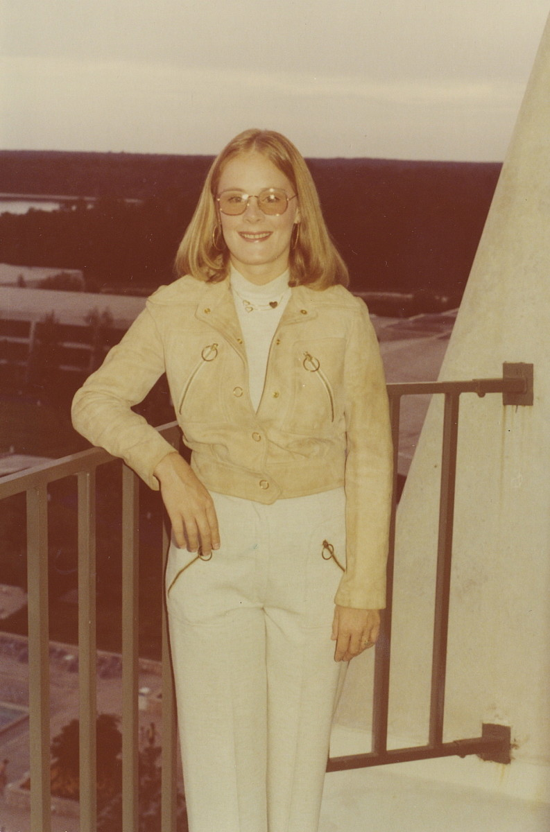 Loose, carefree hair, denim jacket and pants, short waistline, and natural look suggest the 1970s. All you really need to see is the weird yellow tint.
