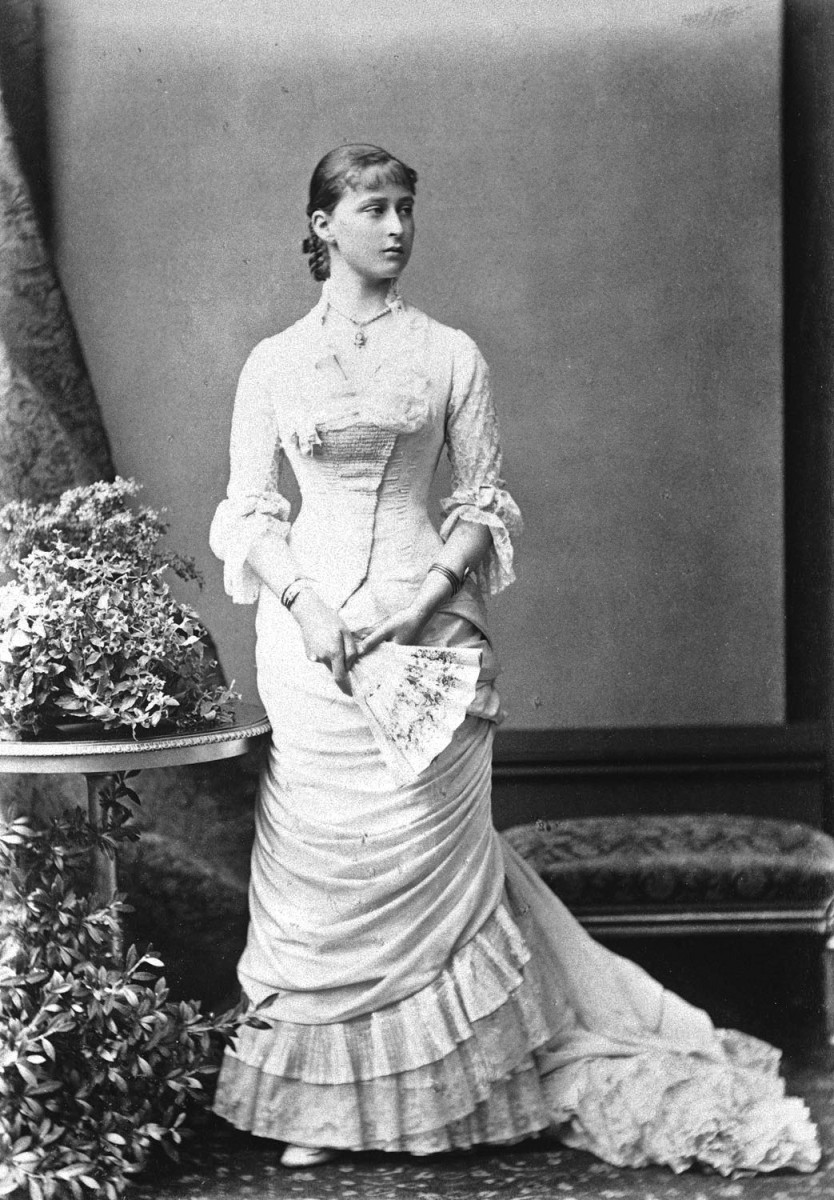 Note the horizontal, slightly diagonal draping of the narrow skirt. Bodice flares below the waist and fits the hips. Also note bangs indicating. Circa early 1880s