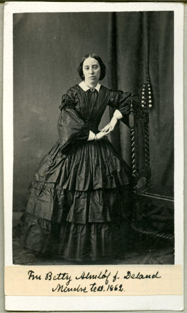 1860s: Pagoda sleeves, low set shoulder line, flounced hoop skirt, and central part in her hair suggest this picture was taken in the 1860s.