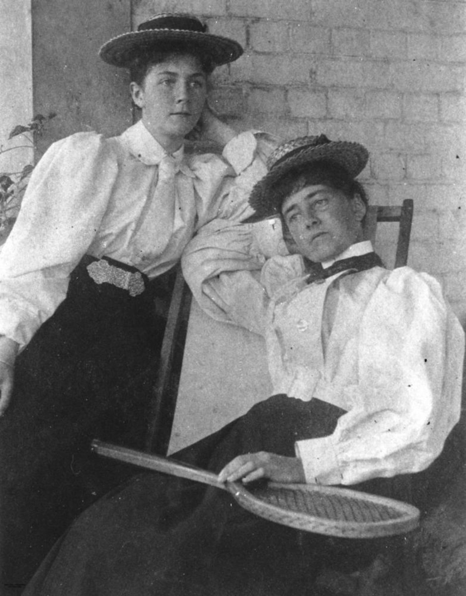 Note large sleeves; light blouse tucked in dark skirt, ties, and straw boater hats suggest the 1890s.