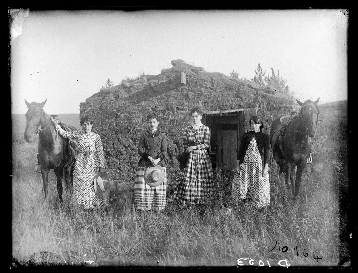 The Chrisman sisters pose in front of a sod house.