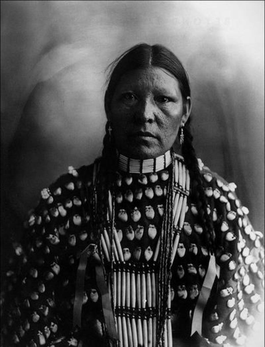 Freckle Face, an Arapaho woman in a shirt decorated with elk teeth, wearing hairpipe jewelry