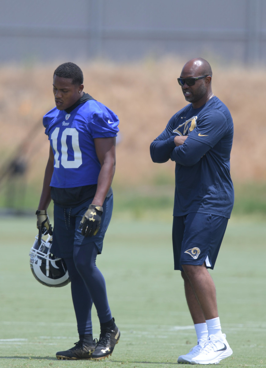 Former St. Louis Rams wide receiver, Torry Holt (right), talks with Los Angeles Rams receiver, Pharoh Cooper, at organized team activities at Cal Lutheran University in June 2018.