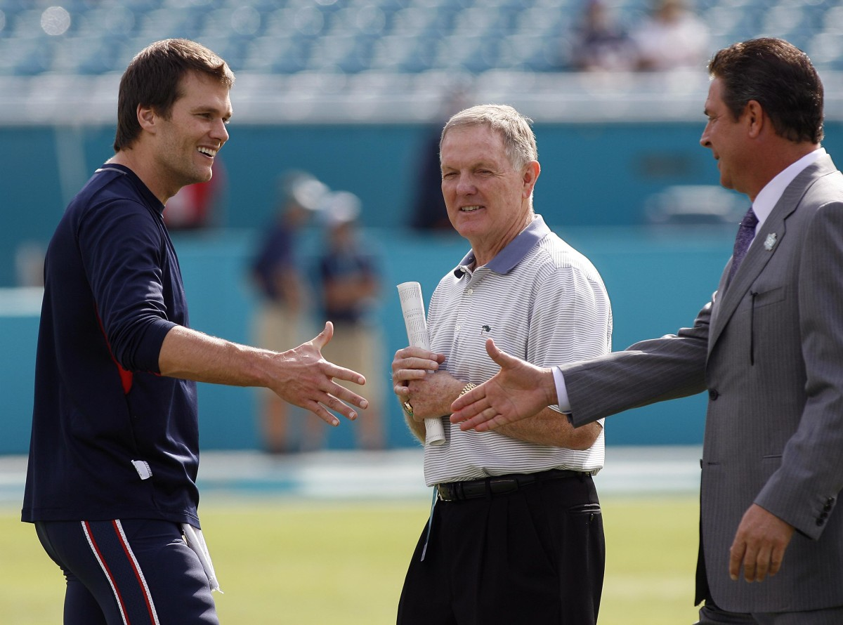 Former Miami Dolphins quarterbacks, Bob Griese (center) and Dan Marino (right), greet New England Patriots quarterback, Tom Brady (left), before the 2016 regular-season finale. Combined, the trio has thrown for more than 150,000 yards.