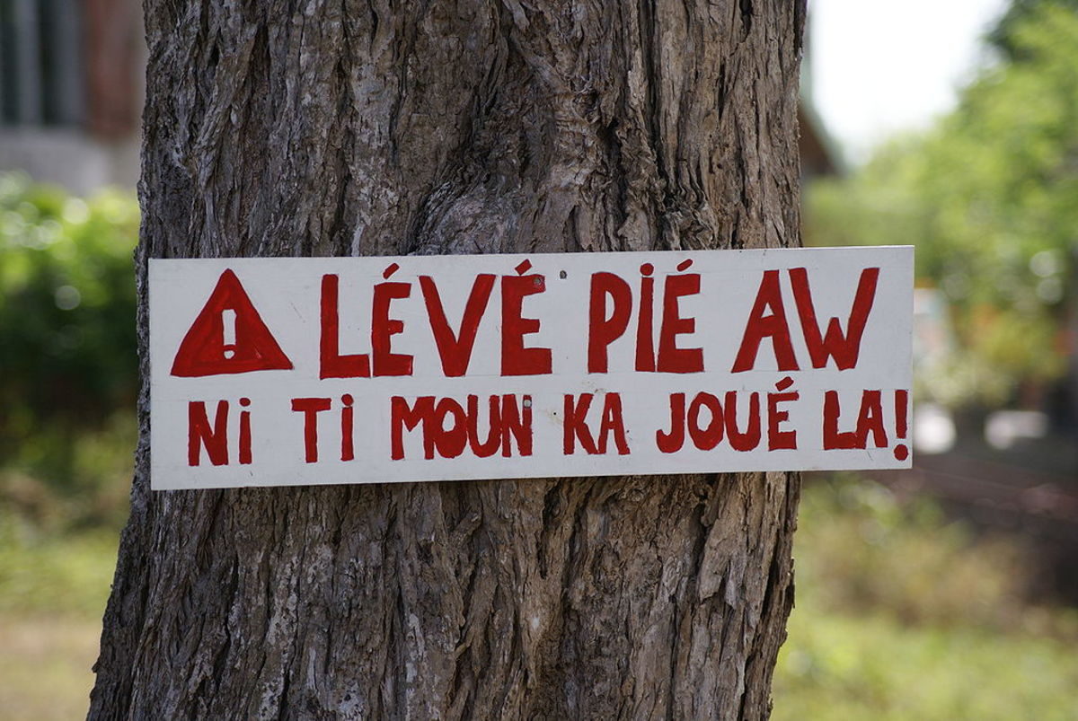 "This sign in Guadeloupe Creole has a literal translation that says ""Lift your foot [from the gas pedal]. There are children playing here."""