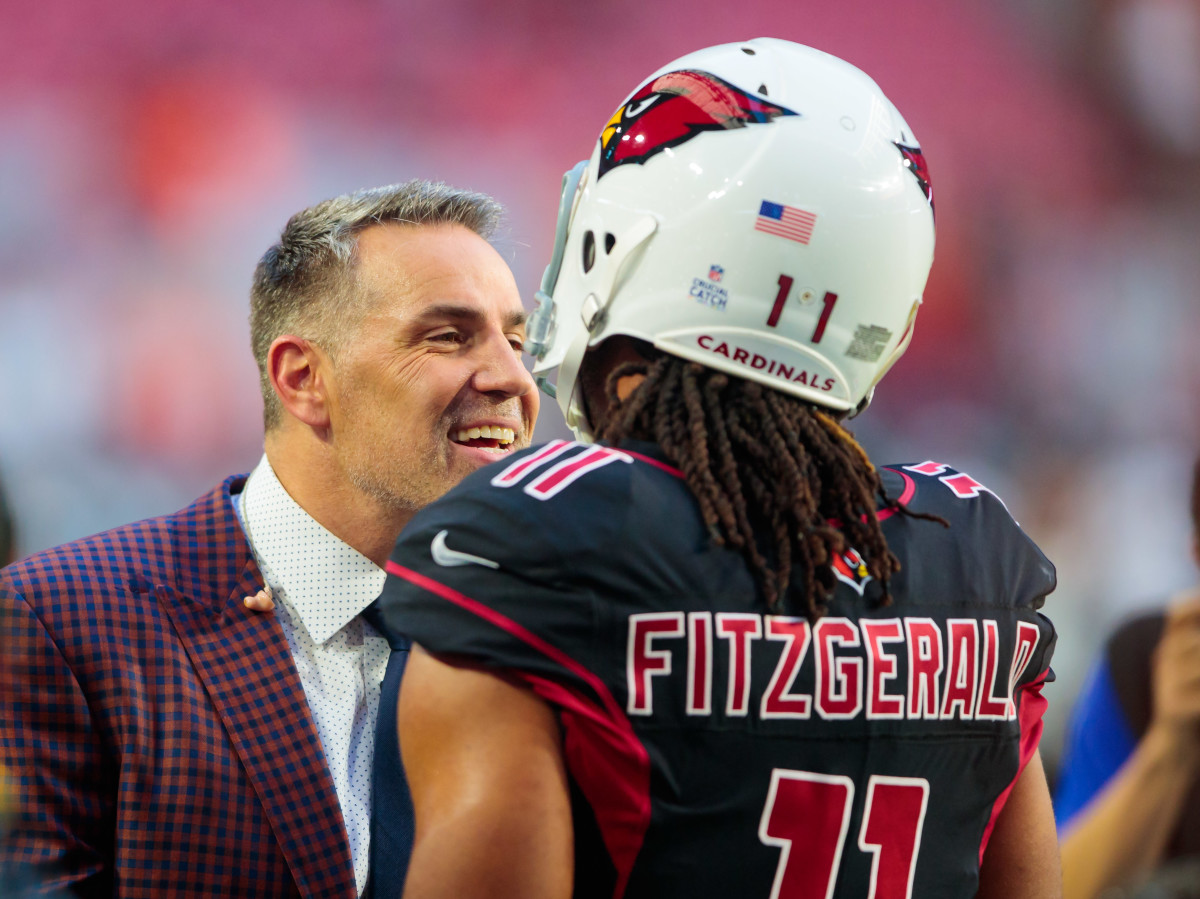 Former Arizona Cardinals quarterback and Pro Football Hall of Famer, Kurt Warner (left), talks with wide receiver Larry Fitzgerald prior to a 2018 game against Denver. Warner and Fitzgerald are the best in team history at their respective positions.