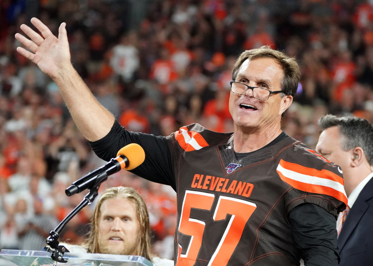 Former Cleveland Browns linebacker, Clay Matthews Jr. (57), speaks as he is inducted into the Browns Ring of Honor at halftime of a 2019 game against the Los Angeles Rams. His son and Rams linebacker, Clay Matthews III, can be seen in the background.