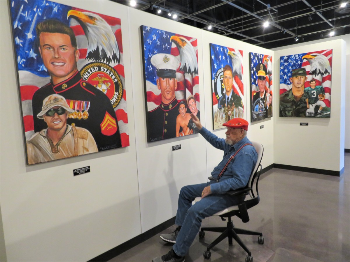 Artist Ken Pridgeon pointing at some of his portraits