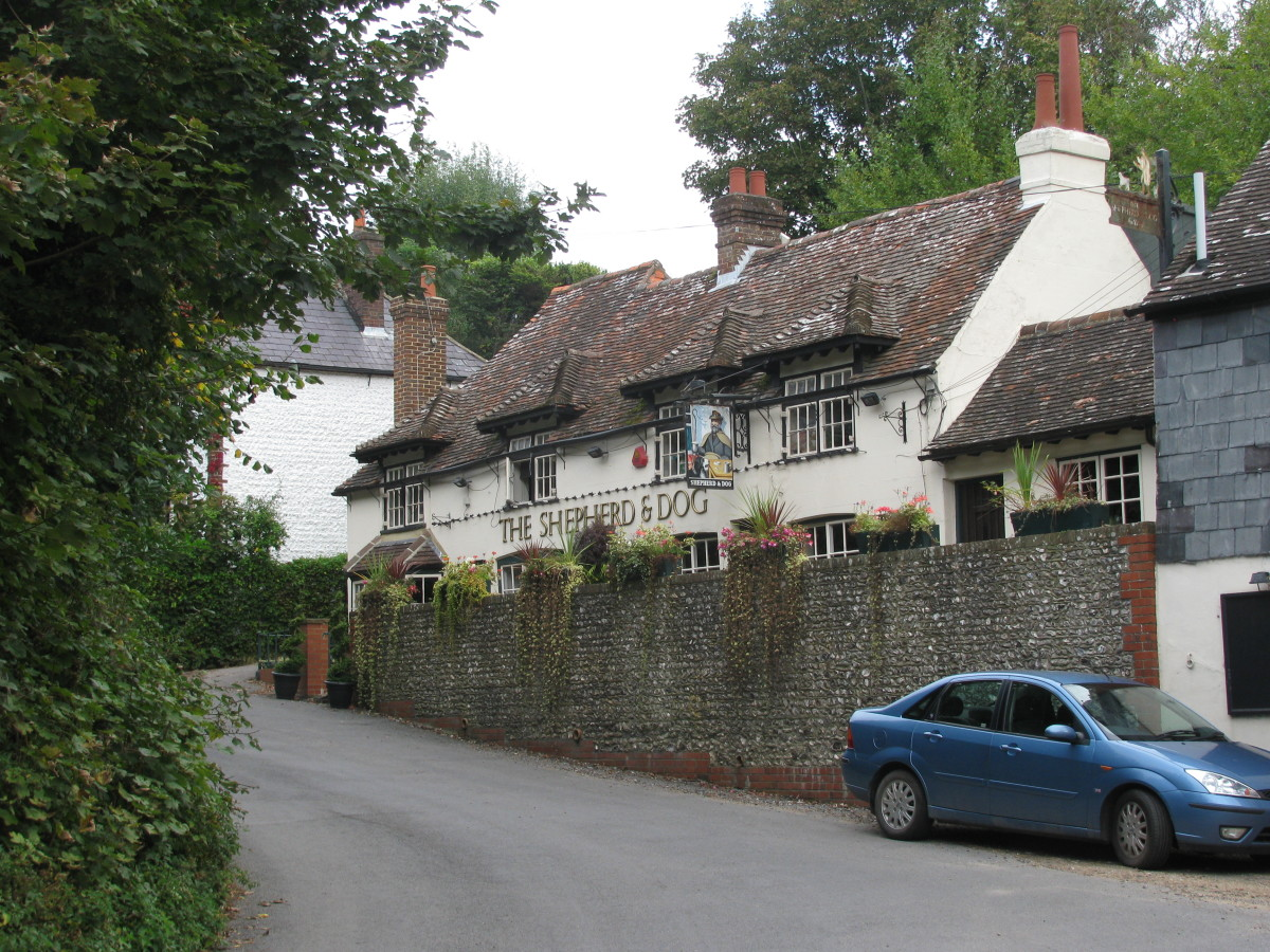 The Shepherd & Dog in Fulking, Sussex; a path to the right starts its ascent to the top of the Sussex Downs