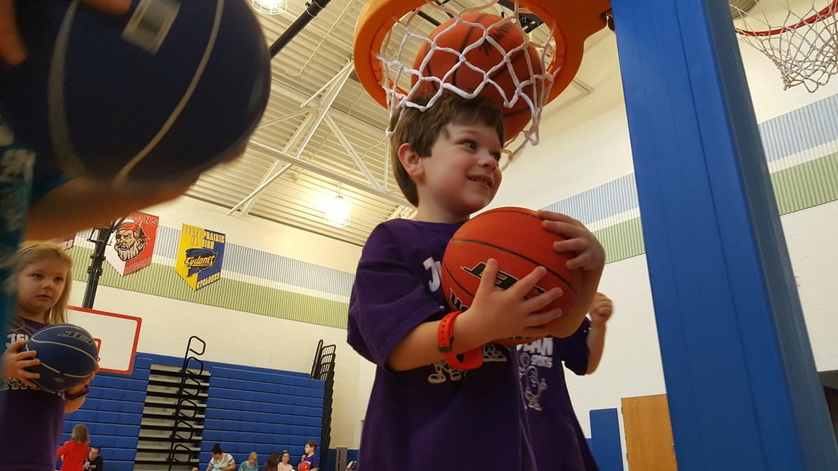 Boy standing with basketball on his head