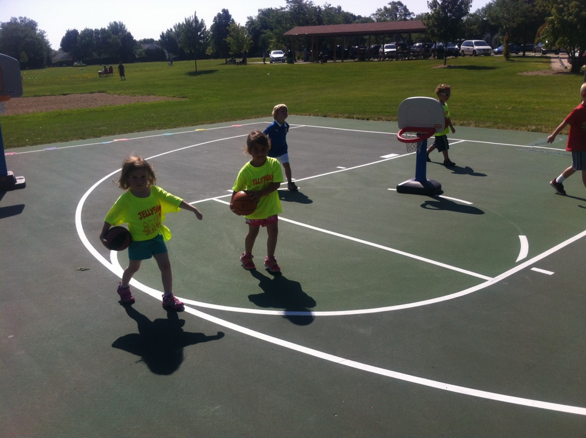 Young children practice dribbling a basketball without dribbling and carrying the ball on their pocket.
