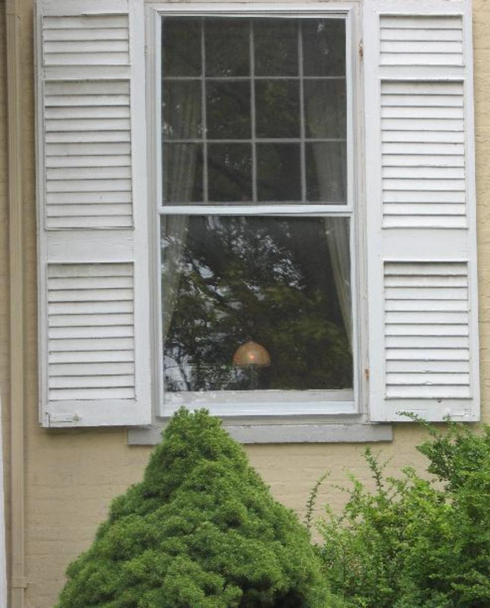 A glowing Candle in the window of the house in Canandaigua, New York that still awaits the return of the son who went off to fight in World War I and never returned.