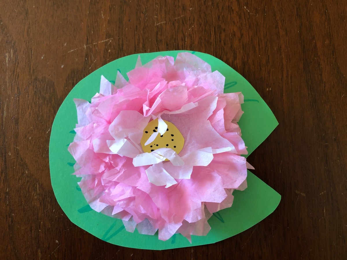 Glue the first piece of tissue paper to the construction paper, then continue gluing each additional piece on top of the previous piece. Glue a small circle of yellow construction paper in the center and fluff the petals.